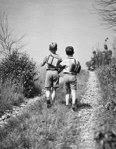 Rear view of two schoolboys walking together along field path